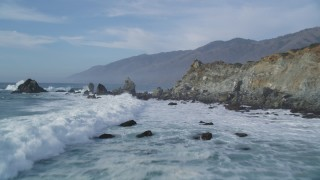 DFKSF03_078 - 5K stock footage aerial video of flying over waves crashing into rock formations, San Simeon, California