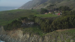DFKSF03_083 - 5K stock footage aerial video fly over coast, approach an oceanfront home, reveal barns, San Simeon, California