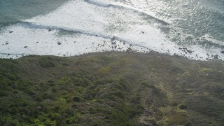 DFKSF03_085 - 5K stock footage aerial video of a bird's eye view of ocean waves rolling toward coastal cliffs, Big Sur, California