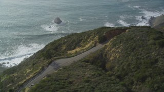 DFKSF03_087 - 5K stock footage aerial video track white convertible on Highway 1, above coastal cliffs, Big Sur, California