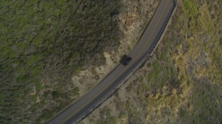 DFKSF03_088 - 5K stock footage aerial video of tracking a black SUV on Highway 1, above coastal cliffs, Big Sur, California