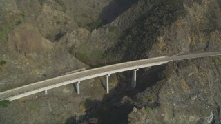 DFKSF03_089 - 5K stock footage aerial video of flying by a small bridge on Highway 1, above coastal cliffs, Big Sur, California