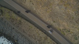 DFKSF03_090 - 5K stock footage aerial video of a bird's eye view of black cars on Highway 1, above coastal cliffs, Big Sur, California