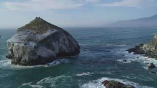 DFKSF03_094 - 5K stock footage aerial video approach and flyby a large rock formation off the coast, Big Sur, California