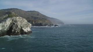 DFKSF03_095 - 5K stock footage aerial video orbit a large rock formation off the coast, reveal coastal cliffs, Big Sur, California