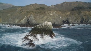 DFKSF03_096 - 5K stock footage aerial video fly over a large rock formation and pan across coastal cliffs, Big Sur, California