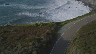 DFKSF03_098 - 5K stock footage aerial video of flying over Highway 1 coastal road, and tilt to ocean waves, Big Sur, California