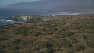 DFKSF03_100 - 5K stock footage aerial video approach and fly over coastal cliffs, Big Sur, California