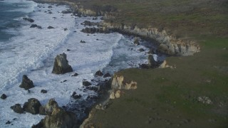 DFKSF03_102 - 5K stock footage aerial video pan from bird's eye view of ocean waves, reveal coastal cliffs, rock formations, Big Sur, California