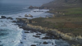 DFKSF03_103 - 5K stock footage aerial video tilt from ocean waves, approach rugged coastal cliffs, rock formations, Big Sur, California