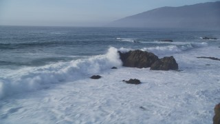 DFKSF03_106 - 5K stock footage aerial video of panning across tall waves crashing into rock formations, Big Sur, California