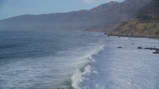 DFKSF03_107 - 5K stock footage aerial video of flying over tall waves, pan right revealing coastal cliffs, Big Sur, California