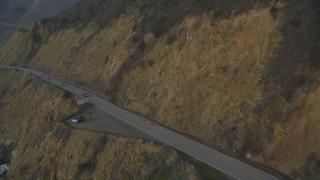 DFKSF03_108 - 5K stock footage aerial video of flying over coastal cliffs, revealing Highway 1 coastal road, Big Sur, California
