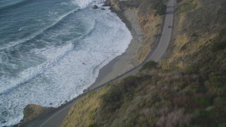 DFKSF03_109 - 5K stock footage aerial video of tilting from Highway 1 coastal road to cliffs to the coastline, Big Sur, California