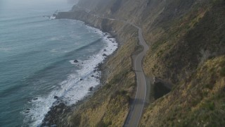 DFKSF03_111 - 5K stock footage aerial video of following Highway 1 coastal road on cliffs, tilt to wider view of coastline, Big Sur, California