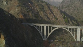 DFKSF03_115 - 5K stock footage aerial video of flying over ocean kelp to reveal small bridge on Highway 1 and cliffs, Big Sur, California