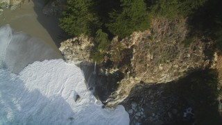DFKSF03_117 - 5K stock footage aerial video of approaching McWay Falls, tilt to bird's eye of waves crashing, Big Sur, California