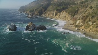 DFKSF03_118 - 5K stock footage aerial video tilt from rock formations in the ocean to reveal coastal cliffs, Big Sur, California