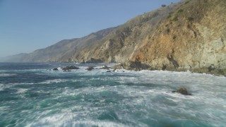 DFKSF03_121 - 5K stock footage aerial video of flying low over the ocean by coastal cliffs, Big Sur, California