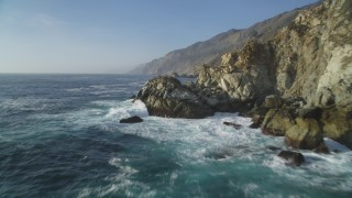 DFKSF03_123 - 5K stock footage aerial video of flying low beside coastal cliffs and over crashing waves, Big Sur, California