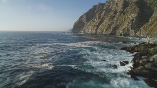 DFKSF03_125 - 5K stock footage aerial video of flying low over the ocean past coastal cliffs, Big Sur, California