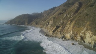 DFKSF03_127 - 5K stock footage aerial video of flying over waves rolling into the base of coastal cliffs, Big Sur, California