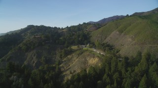 DFKSF03_129 - 5K stock footage aerial video of approaching hills beside Highway 1 and roadside restaurant, Big Sur, California
