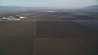 DFKSF03_138 - 5K stock footage aerial video of flying by a landscape of vast farm fields, Salinas, California