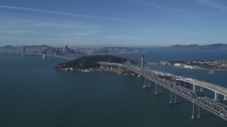 DFKSF05_009 - 5K stock footage aerial video approach Bay Bridge, Yerba Buena Island, with view of Downtown San Francisco, California