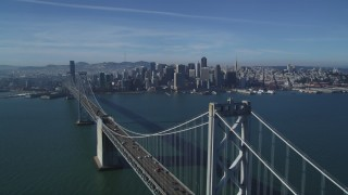 DFKSF05_012 - 5K stock footage aerial video fly over Bay Bridge to approach skyline of Downtown San Francisco, California