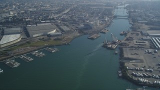 DFKSF05_098 - 5K stock footage aerial video flyby warehouses and factories on both sides of the Oakland Estuary, Oakland, California