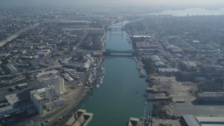 DFKSF05_099 - 5K stock footage aerial video fly over the Oakland Estuary toward bridges and factories, Oakland, California