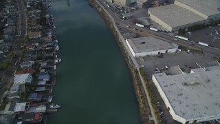 DFKSF06_003 - 5K stock footage aerial video of flying over estuary and warehouses, reveal factory, Fruitvale Bridge, Oakland Estuary, California