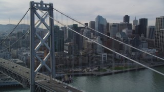 DFKSF06_026 - 5K stock footage aerial video of flying over the Bay Bridge toward skyscrapers in Downtown San Francisco, California