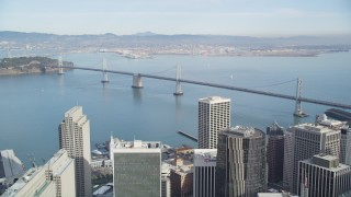 DFKSF06_045 - 5K stock footage aerial video tilt from California Street revealing skyscrapers and Bay Bridge, Downtown San Francisco, California