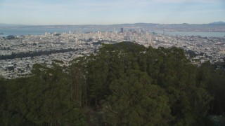 DFKSF06_073 - 5K stock footage aerial video tilt from Mount Sutro forest to reveal skyscrapers in Downtown San Francisco, California