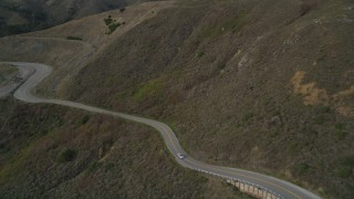 DFKSF06_108 - 5K stock footage aerial video of flying over Highway 1 at the base of mountains, Marin County, California