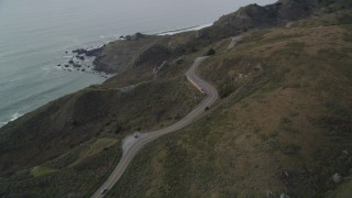 DFKSF06_109 - 5K stock footage aerial video pan across and fly over Highway 1 on the coast, Marin County, California
