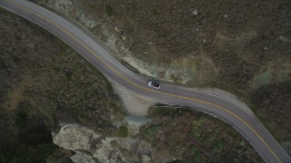 DFKSF06_111 - 5K stock footage aerial video of a bird's eye view of a silver convertible on Highway 1, Marin County, California