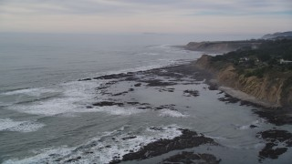 DFKSF06_116 - 5K stock footage aerial video of flying by ocean waves near coastal cliffs, Bolinas, California