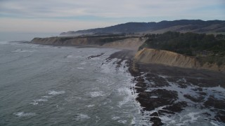 DFKSF06_117 - 5K stock footage aerial video of flying past waves near coastal cliffs, Bolinas, California