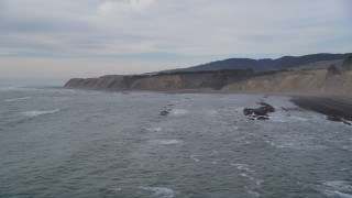 DFKSF06_118 - Aerial stock footage of 5K aerial stock of descending towards waves near coastal cliffs, Bolinas, California