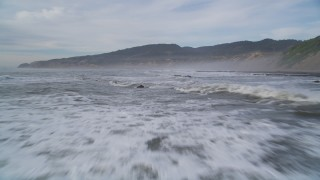 DFKSF06_122 - 5K stock footage aerial video of flying low over waves near coastal cliffs, Bolinas, California