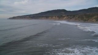DFKSF06_123 - 5K stock footage aerial video of flying low over waves while approaching coastal cliffs, Bolinas, California