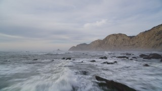 DFKSF06_126 - 5K stock footage aerial video of flying low over ocean and rocks near coastal cliffs, Bolinas, California