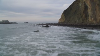 DFKSF06_130 - 5K stock footage aerial video of flying low over ocean panning across coastal cliffs to reveal rock formations, Bolinas, California