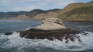 DFKSF06_132 - 5K stock footage aerial video of circling a rock formation and ascending toward coastline, Bolinas, California
