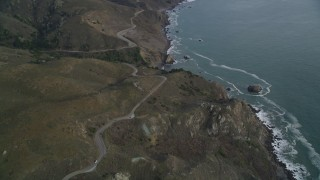 DFKSF06_151 - 5K stock footage aerial video of flying over Highway 1 winding around coastal cliffs, Marin County, California