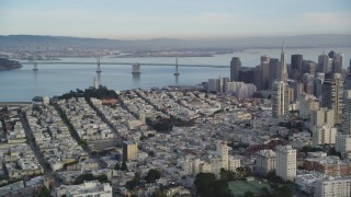 DFKSF06_168 - 5K stock footage aerial video approach Coit Tower, Bay Bridge, pan skyscrapers in Downtown San Francisco, California