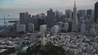 DFKSF06_173 - 5K stock footage aerial video orbit Coit Tower, reveal Transamerica Pyramid and skyscrapers, Downtown San Francisco, California